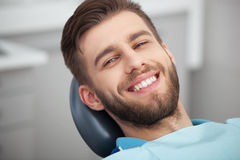 Portrait of happy patient in dental chair. Stock Image