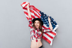 Portrait of a happy patriotic girl holding USA flag. Portrait of a happy excited girl holding USA flag isolated over gray background Royalty Free Stock Image