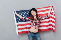 Portrait of a happy patriotic girl holding USA flag. Isolated over gray background Stock Photos