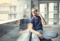 Glad old man talking by mobile phone. Portrait of happy pensioner resting on windowsill and communication by cellphone. Copy space in left side Stock Image