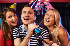 In karaoke bar. Portrait of happy people singing in microphone in the karaoke bar Stock Photo