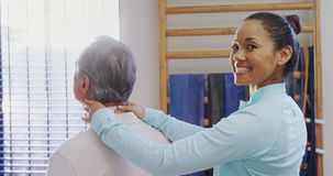 Portrait of happy physiotherapist giving neck massage to senior patient 4k stock video