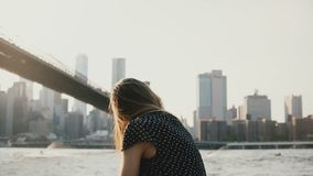 Portrait of happy playful European girl posing, smiling at camera near sunset Brooklyn Bridge river panorama, NYC 4K. Casual young excited woman in romantic stock video footage