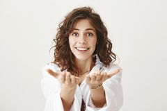 Portrait of happy pleasant young female stretching hands at camera, being moved by something, standing against gray. Background in trendy outfit. Aunt wants to royalty free stock photography