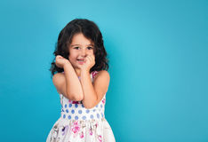 Portrait of a happy, positive, smiling, little girl. Blue background Royalty Free Stock Photography