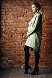 Portrait of happy pregnant brunette girl posing against brick wall. royalty free stock images