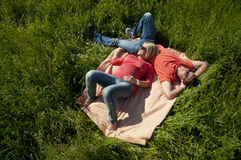 Portrait of a happy pregnant couple lying on blanket Stock Images