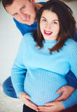 Portrait of happy pregnant couple relaxing at home Royalty Free Stock Images