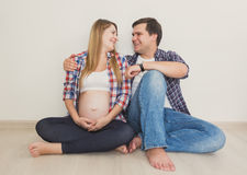 Portrait of happy pregnant couple sitting on floor and looking a Stock Images
