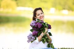 Portrait of happy pregnant woman with bouquet of lilacs on the b Royalty Free Stock Photography