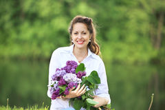 Portrait of happy pregnant woman with bouquet of lilacs Stock Image