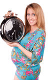 Portrait of happy pregnant woman with clock Royalty Free Stock Image