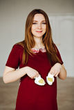 Portrait of a happy pregnant woman holding baby shoes Stock Photos