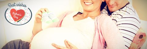 Composite image of portrait of a happy pregnant woman holding baby shoes and of her husband on a sof stock images