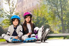 Happy preteen boy and girl in roller skates. Portrait of happy preteen boy and girl in roller skates, sitting on the floor outdoors at sunny day Stock Images