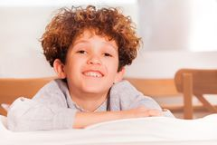 Happy preteen boy sitting backwards on white sofa. Portrait of happy preteen boy sitting backwards on white sofa in the lounge room Stock Images