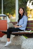 Portrait of a happy pretty asian female student. Holding laptop computer while sitting on the bench at the park Royalty Free Stock Images