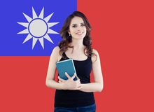 Portrait of happy pretty girl against the Taiwan flag background. Young woman learning chinese language and traveling in Taiwan.  stock image