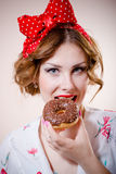 Portrait of happy pretty girl beautiful blond young woman with excellent dental care teeth having fun eating donut. Image of pinup girl beautiful blond young Royalty Free Stock Photography