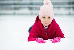 Portrait of happy pretty little girl plainf with snow in winter Stock Photos