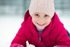 Portrait of happy pretty little girl plainf with snow in winter Royalty Free Stock Photo