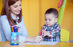 Portrait of happy pretty mother with her toddler son drawing Royalty Free Stock Photo