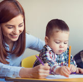 Portrait of happy pretty mother with her toddler son drawing Stock Images