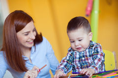 Portrait of happy pretty mother with her toddler son drawing Stock Photography