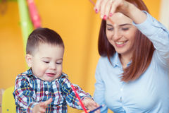 Portrait of happy pretty mother with her toddler son drawing Royalty Free Stock Images