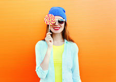 Portrait of happy pretty smiling woman and lollipop over colorful orange. Background Stock Photos