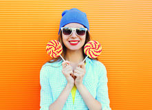 Portrait happy pretty smiling woman and lollipop over colorful orange. Background Stock Photos