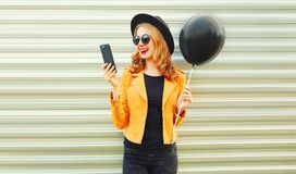 happy pretty smiling woman with phone holding black helium air balloon royalty free stock image