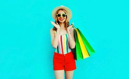 Portrait happy pretty smiling woman with shopping bags in colorful t-shirt, summer round hat on blue wall. Background royalty free stock photos
