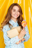 Portrait of a happy pretty student girl holding sweet candy over Royalty Free Stock Photography