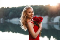 Portrait of a happy pretty woman with a bouquet of peony. On the. Background of the sea. Sunset Royalty Free Stock Photo