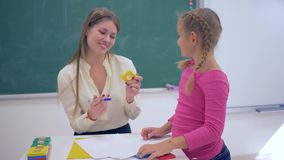 Portrait of happy professional teacher female with smart schoolkid girl with plastic figures in hand near board in. Classroom of elementary school stock video footage