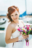 Portrait of happy red-haired bride with a bouquet in hand Stock Image