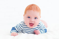 Portrait of happy redhead baby boy lying on belly Stock Photos