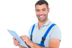 Portrait of happy repairman using digital tablet. On white background Royalty Free Stock Image