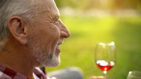 Portrait of happy retired male smiling and drinking wine with wife, anniversary. Stock photo stock images