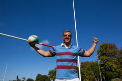 Portrait of happy rugby player holding ball against blue sky. Portrait of happy rugby player holding ball with arms raised by goal post against blue sky Royalty Free Stock Photos