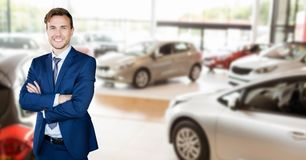 Portrait of happy salesman standing in car showroom stock image