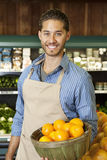 Portrait of a happy salesperson with basket full of oranges in market Stock Photography