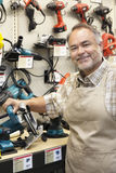 Portrait of a happy salesperson with electric saw in hardware store Royalty Free Stock Images