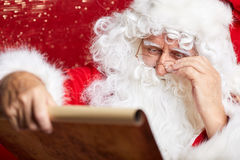 Portrait of happy Santa Claus holding Christmas letter Stock Images