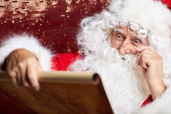 Portrait of happy Santa Claus holding Christmas letter Royalty Free Stock Photo