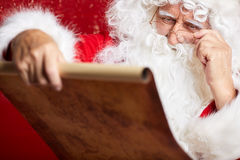 Portrait of happy Santa Claus holding Christmas letter Royalty Free Stock Photos