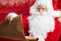 Portrait of happy Santa Claus holding Christmas letter Royalty Free Stock Images