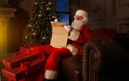 Portrait of happy Santa Claus sitting at his room at home near Christmas tree and reading Christmas letter or wish list. Portrait of happy Santa Claus sitting Royalty Free Stock Photography