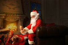 Portrait of happy Santa Claus sitting at his room at home near Christmas tree and reading Christmas letter or wish list. royalty free stock images